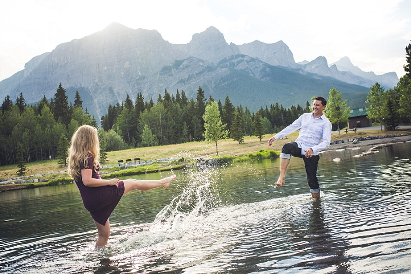 couple kicking up water canmore quarry lake engagement session