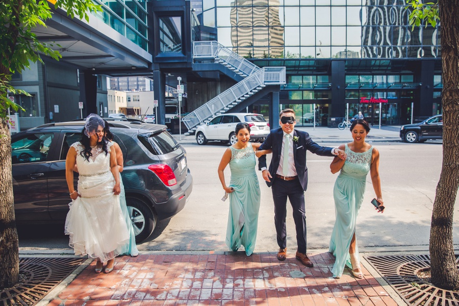 groom blindfolded for first look in calgary wedding photographers