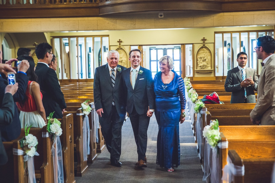groom walking down aisle with parents sacred heart church