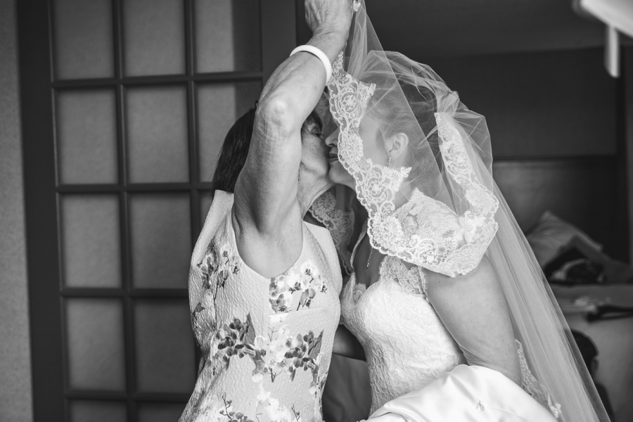 carriage house inn calgary wedding photographer bride kissing mom over veil