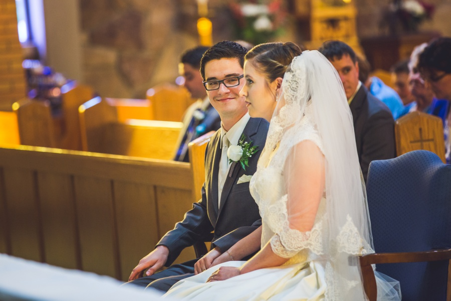 st anthony's parish calgary latin wedding photographer groom smiling at bride