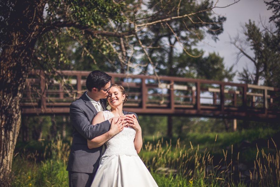 fish creek park calgary latin wedding photographer bride and groom with bridge