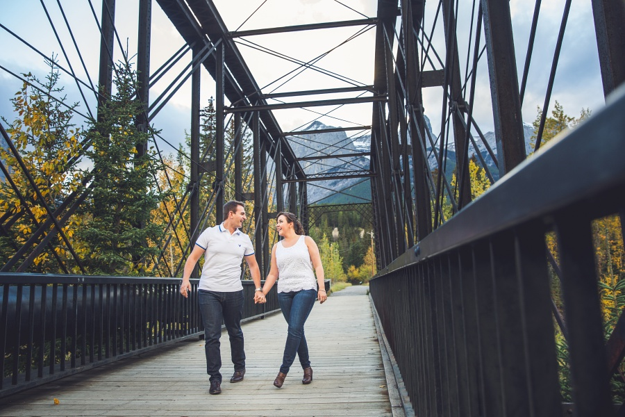 couple walking on engine bridge canmore engagement photos