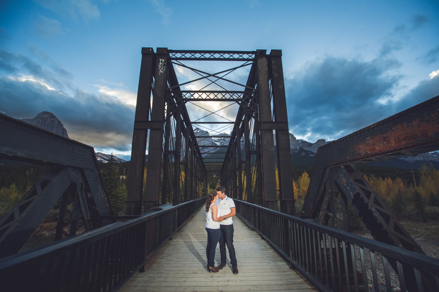 couple kissing on engine bridge canmore engagement photos
