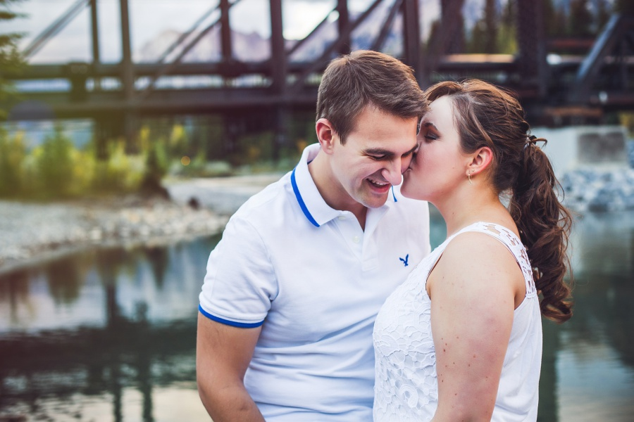 couple kissing by engine bridge lake canmore engagement photos