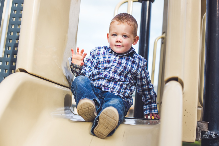 calgary family fall photography boy in plaid shirt down slide