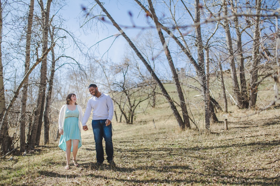 couple walking hand in hand mixed race spring engagement photos calgary