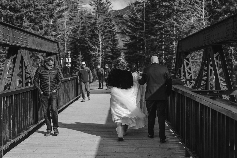 Winter Mountain Canmore Wedding groom helping bride with dress