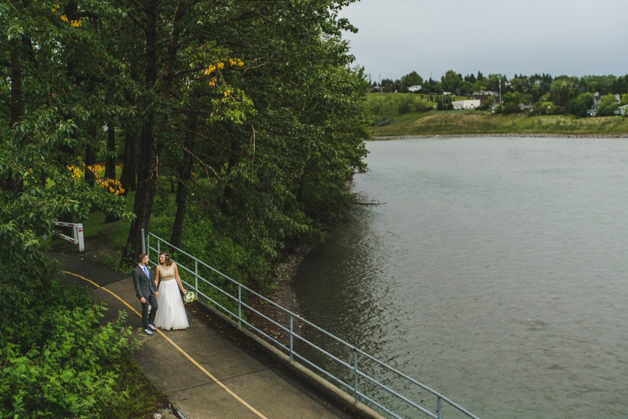 calgary backyard wedding bride groom walking by river