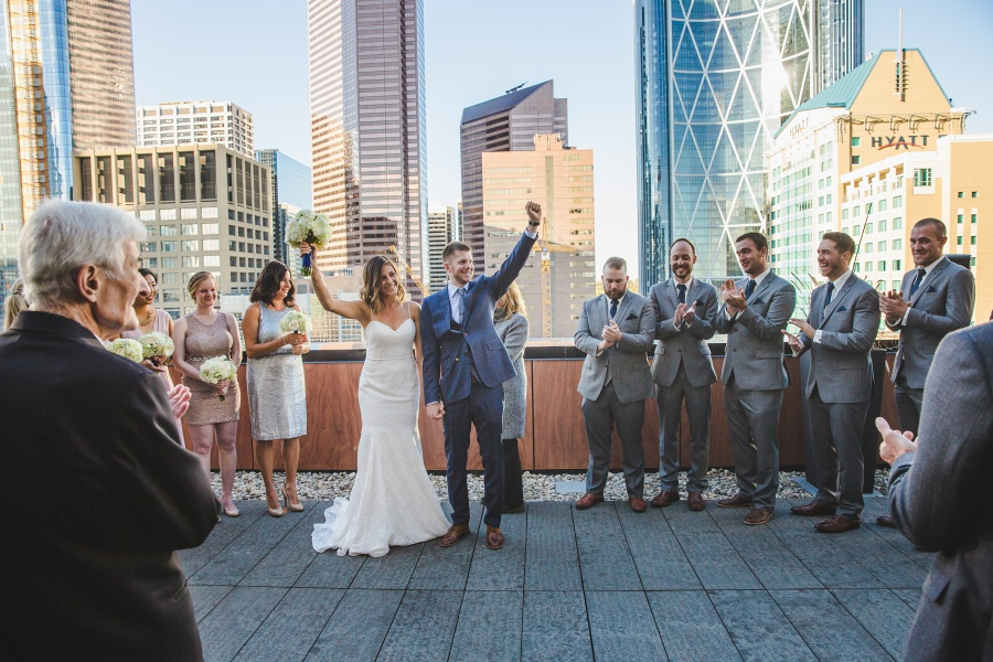 Le Germain Calgary Rooftop Wedding bride groom cheering blue suit