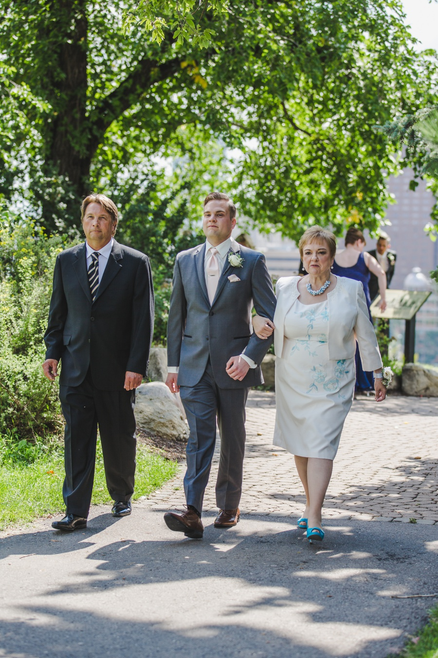 groom grey suit pink tie walking down aisle with parents calgary rotary park wedding