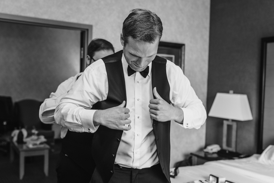 groom putting on vest geeky heritage park wedding calgary