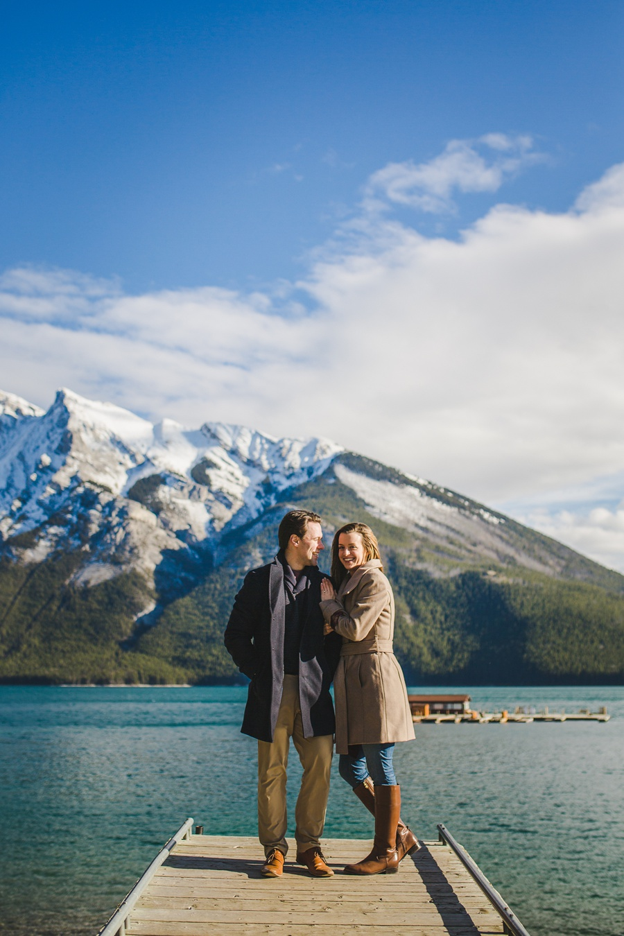 lake minnewanka banff engagement photos in the fall couple on wood bridge