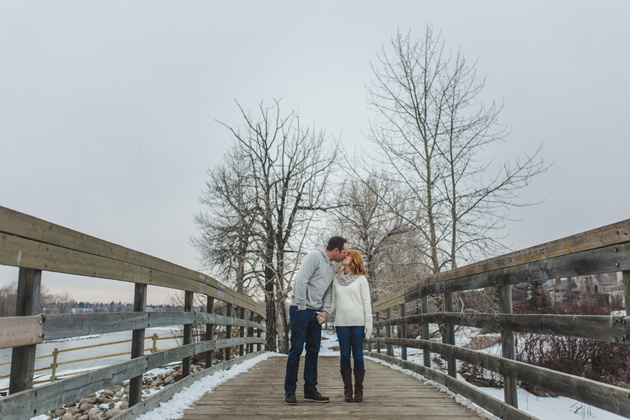 calgary winter engagement photos kiss on bridge trees