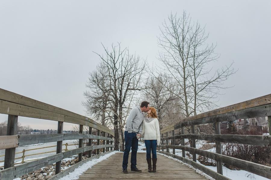 calgary winter engagement photos kiss on bridge trees