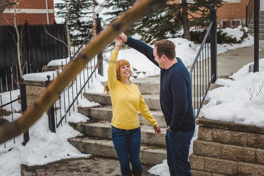 calgary winter engagement photos couple twirling yellow sweater redhead