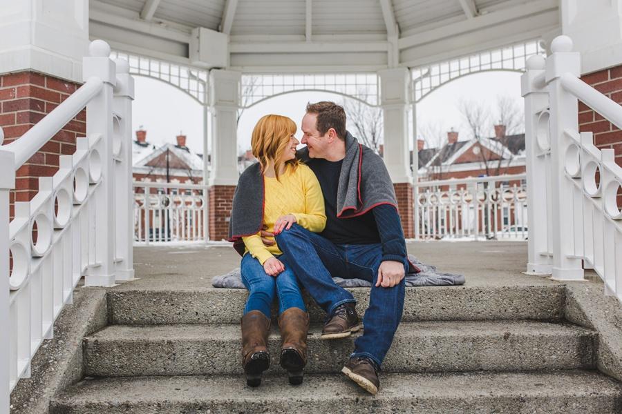 calgary winter engagement photos couple cuddling in blanket gazebo