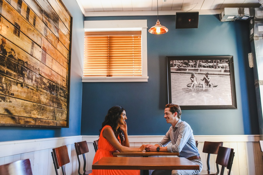 mill street brewpub calgary engagement photos couple holding hands at table