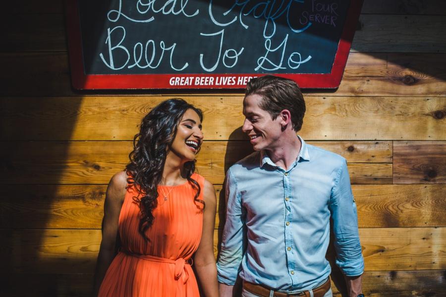 mill street brewpub calgary engagement photos couple laughing orange dress