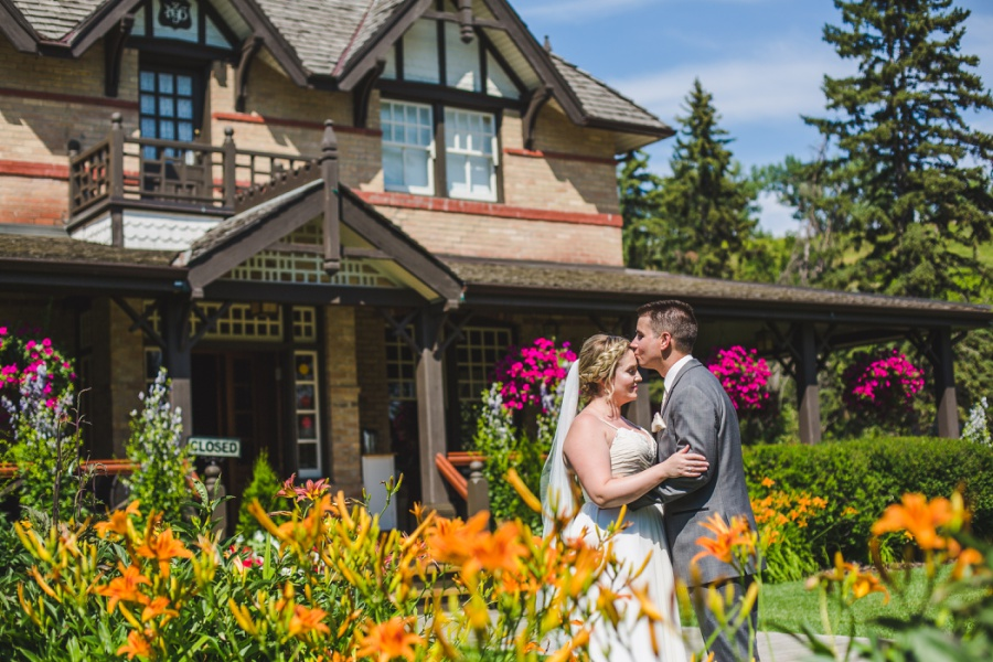 calgary ranche restaurant wedding photographer groom kisses bride forehead