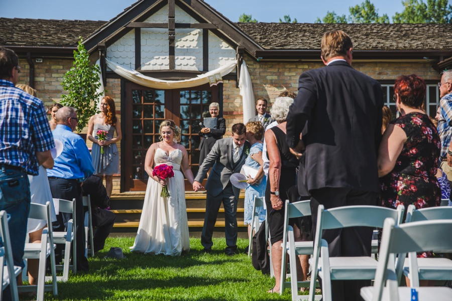 calgary ranche restaurant wedding photographer walking down aisle bride groom