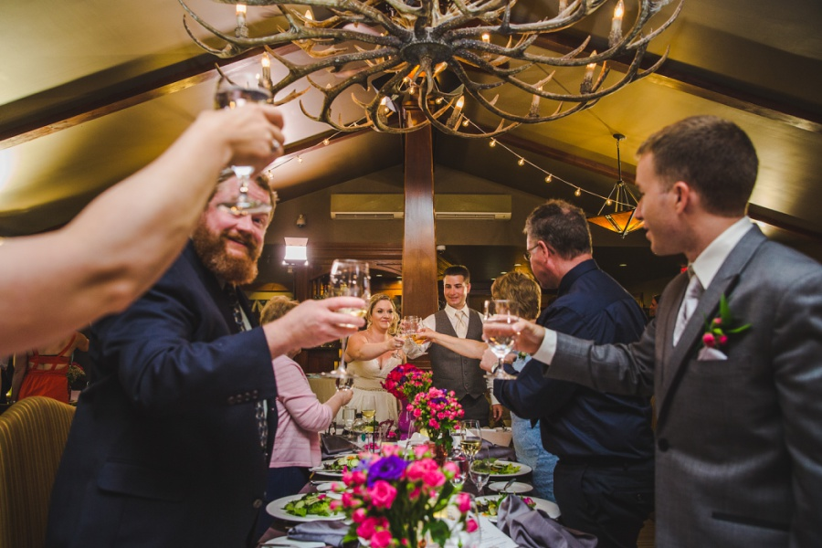 calgary ranche restaurant wedding photographer bride groom cheers toast